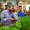 Mr. Logsdon demonstrates the fluorometer with his AP Bio class