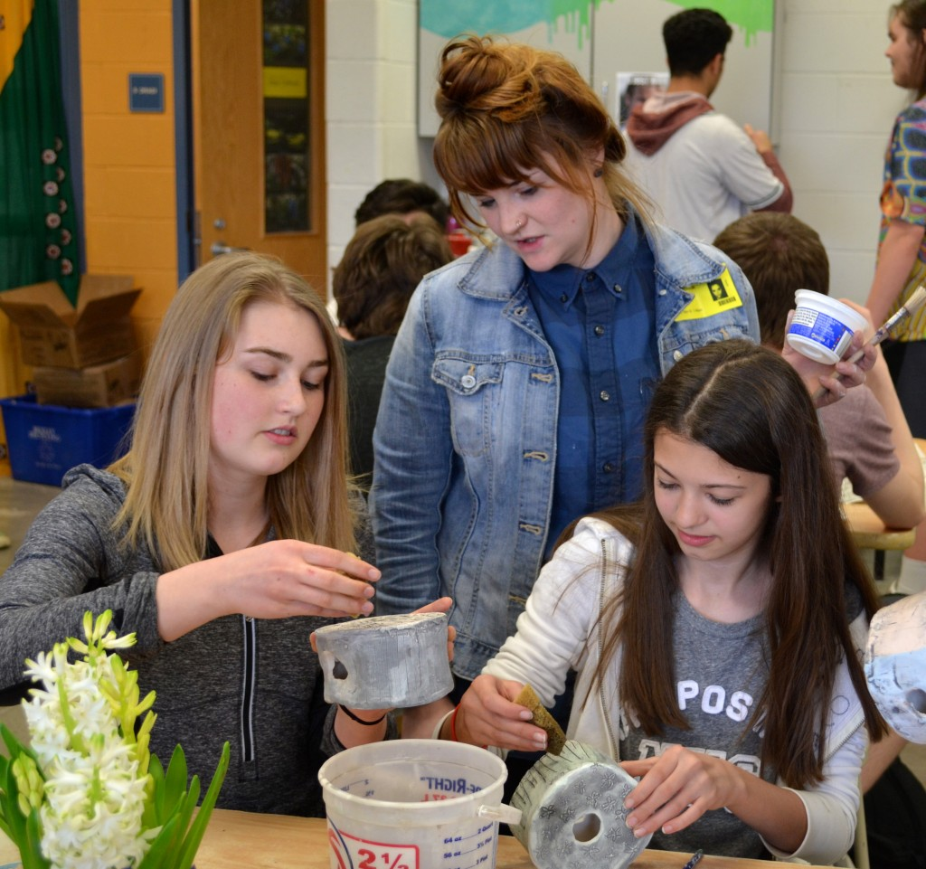 Ceramicist Megs Levasseur (center) provides instruction to art students as they create totems for the garden